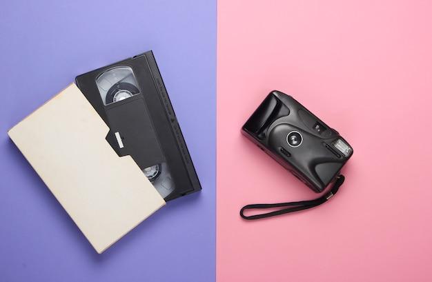 Videocassetta e fotocamera retrò su pastello rosa-viola.