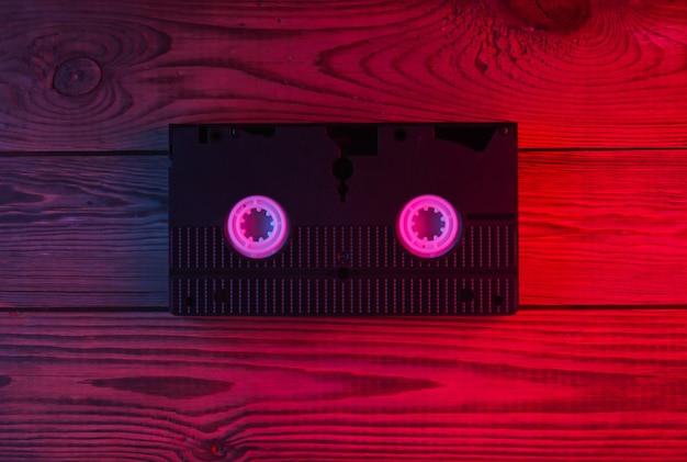 Videocassetta su superficie in legno. luce al neon rossa e blu