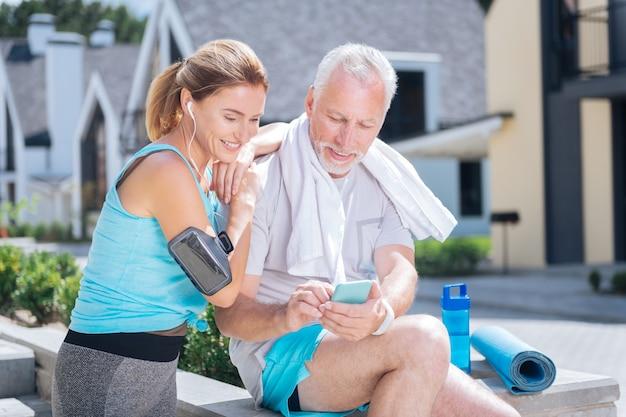Chat video. coppia di uomini d'affari atletici che hanno chat video sul loro smart phone blu con i loro figli insieme