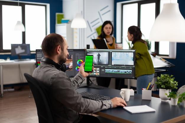Editor video parlando in videochiamata che tiene smartphone con schermo verde, chroma key mock up display isolato prendendo una pausa dal film di ritocco seduto nell'ufficio di avvio
