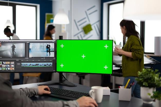 Editor video che utilizza computer con chroma key mock up display isolato