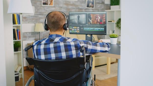 Editor video in sedia a rotelle che lavora alla post produzione del film.