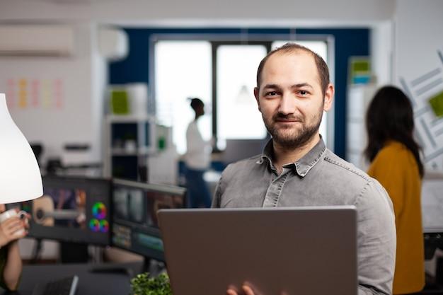Lavoratore dell'editor video in piedi davanti alla telecamera sorridente che lavora nell'ufficio dell'agenzia creativa con un laptop