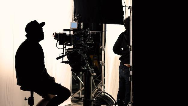 Produzione video dietro le quinte che vede la troupe cinematografica in silhouette riprese o la registrazione di spot televisivi con attrezzature professionali come telecamera ad alta definizione con monitor in studio set.