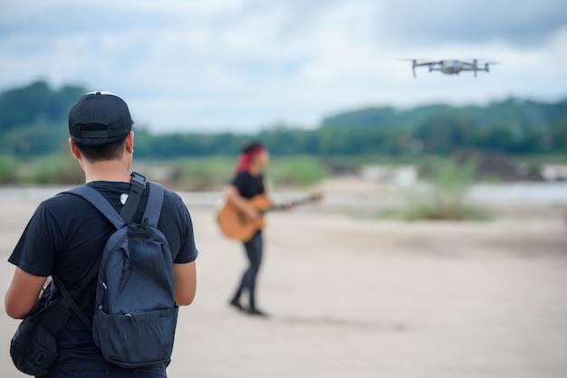 Registrazione video con un aereo drone uomini asiatici che usano video droni per realizzare video musicali