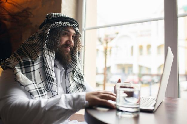 Video chiamata. uomo d'affari arabo che lavora in ufficio, centro affari utilizzando dispositivo, gadget. stile di vita saudita moderno. l'uomo in abiti tradizionali e sciarpa sembra sicuro, impegnato, bello. etnia, finanza.