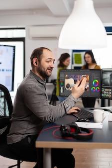 Videografo che discute online con un cliente in possesso di smartphone che modifica filmati di film seduto in agenzia creativa
