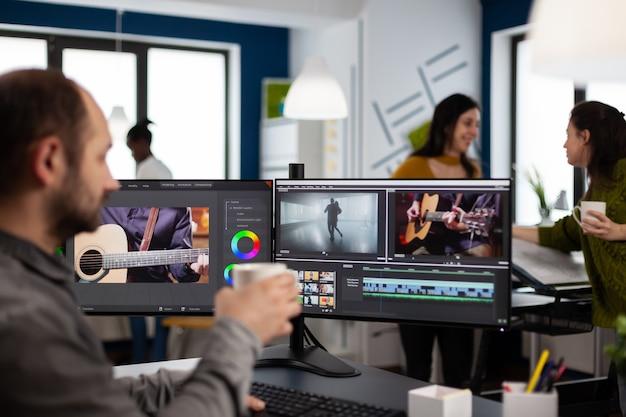 Videografo che modifica il progetto del film bevendo caffè utilizzando un software di post produzione che lavora in un'azienda multimediale digitale con due monitor