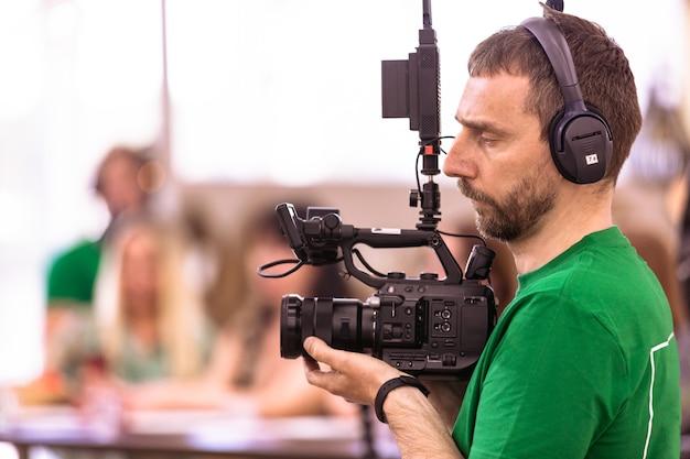 Videografo che gira un film o un programma televisivo in uno studio con una telecamera professionale, nel backstage