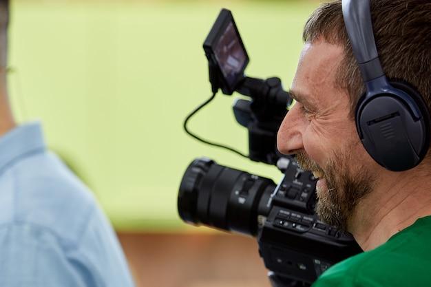 Videografo che gira un film o un programma televisivo con una telecamera professionale, nel backstage.