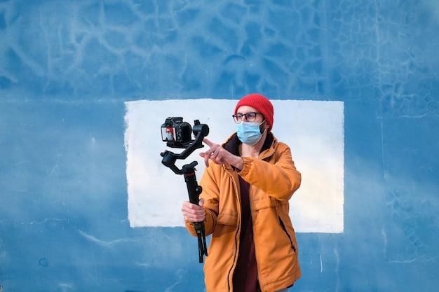 Il videografo che indossa una maschera protettiva configura la sua fotocamera dslr su un giunto cardanico motorizzato