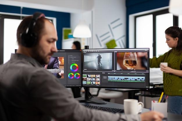 Operatore video con auricolare che lavora con riprese e audio su un pc con due display, prendendo appunti durante la modifica del video del cliente