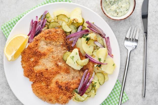 Cotoletta alla viennese con patate e cipolle.