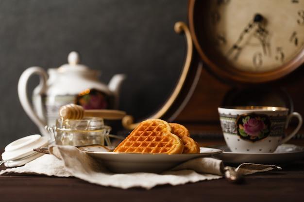 Wafer viennesi sul tavolo scuro con una tazza di tè