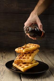 I waffle viennesi vengono versati con lo sciroppo da una bottiglia