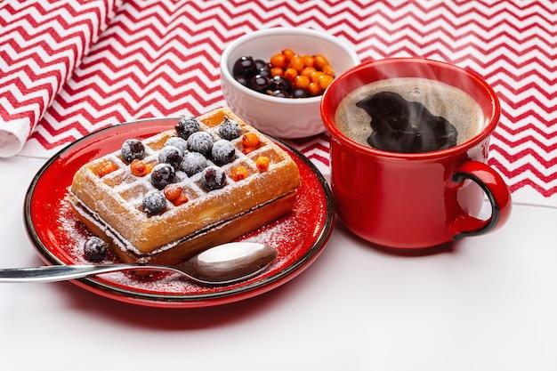 Waffle viennesi cosparsi di polvere e decorati con frutti di bosco. caffè caldo in tazza rossa.
