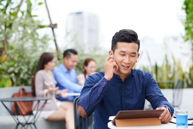 Uomo d'affari vietnamita che ascolta l'altoparlante negli auricolari durante la videochiamata del suo socio in affari