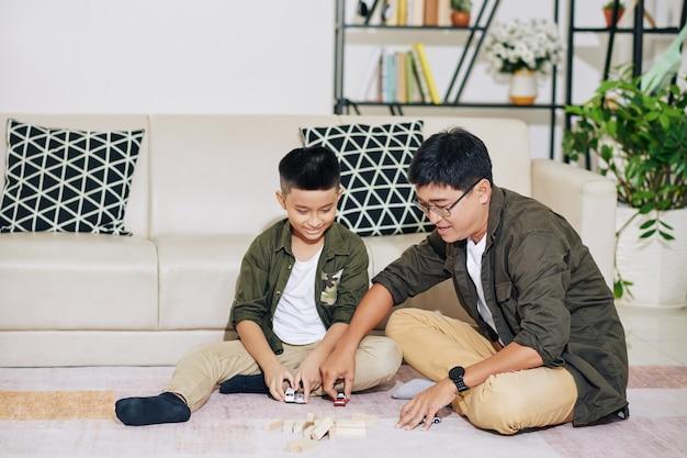 Padre vietnamita e suo figlio preadolescente giocano con macchinine e torri che si schiantano fatte di blocchi di legno
