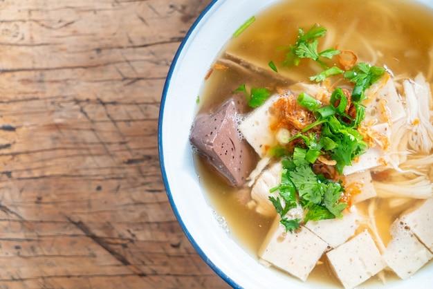 Zuppa di noodle di riso vietnamita con carne di maiale e pollo su tavola di legno