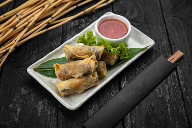 Involtini vietnamiti con spaghetti di riso alle verdure e gamberi con salsa di peperoncino dolce su superficie di legno