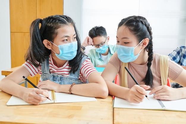 Studentesse vietnamite in maschere mediche seduti alla scrivania in classe e discutendo di compiti difficili