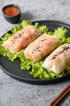 Involtini primavera vietnamiti di gamberi e verdure in carta di riso su sfondo grigio chiaro.