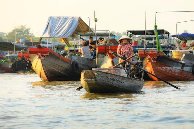 Un venditore vietnamita fila la sua barca sul mercato galleggiante di nga nam nel delta del mekong, vietnam