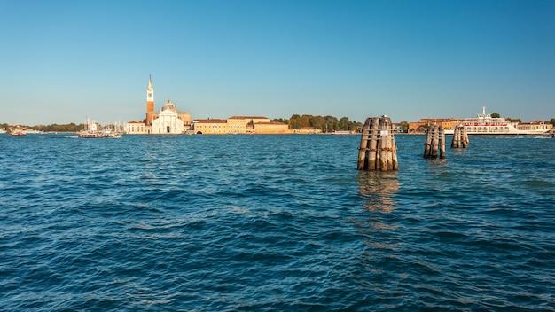 Vista attraverso l'acqua del canale della giudecca dell'isola di san georgio maggiore, con il suo campanile e la chiesa progettata dal palladio, venezia, italia