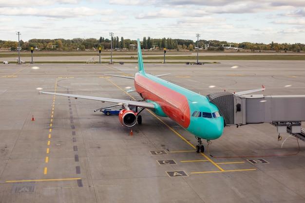 Vista del parcheggio degli aeromobili in aeroporto. l'aereo è in preparazione per la partenza dal personale dell'aeroporto.