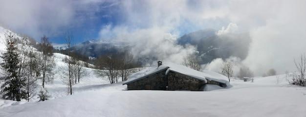 Mostra su chalet alpino nel paesaggio montano innevato e cielo nuvoloso