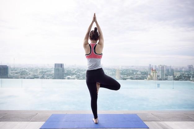 Vista della donna asiatica torna in posa ad albero asana yoga posa