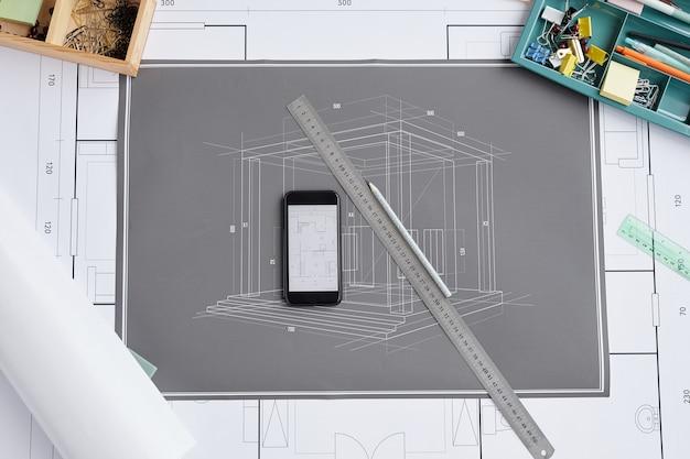 Sopra il fondo di vista delle cianografie e dei piani sul tavolo da disegno sul posto di lavoro degli architetti,