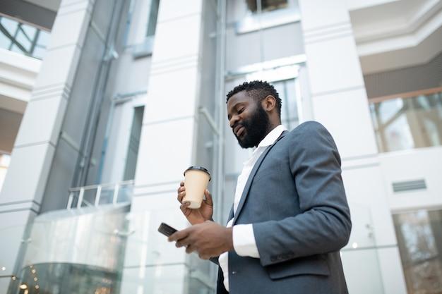 Sotto la vista dell'uomo d'affari nero barbuto in giacca che risponde in messenger e beve caffè in movimento