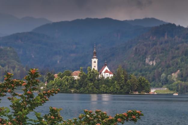 Vista del lago di bled isola di bled con una piccola chiesa di pellegrinaggio montagne sullo sfondo della slovenia