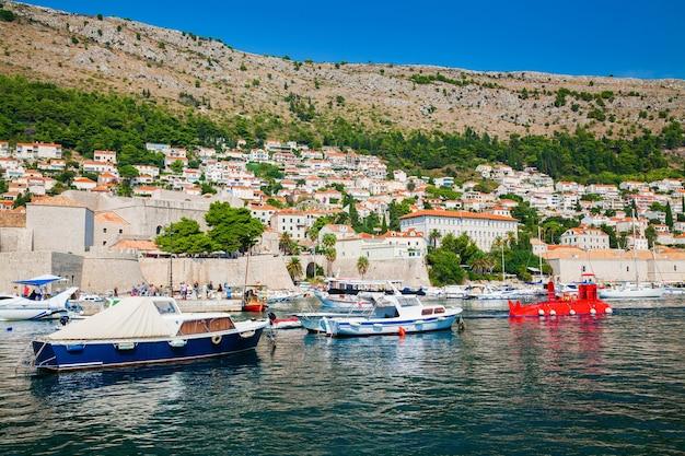 Vista delle barche al porto del porto vecchio di dubrovnik e piccole case al di fuori delle mura della città, croazia