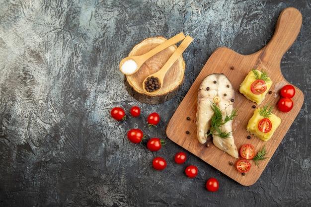 Vista dall'alto di farina di grano saraceno di pesce bollito servita con pomodori formaggio verde su tagliere di legno spezie sulla superficie del ghiaccio