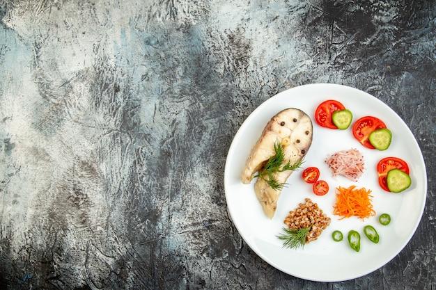 Sopra la vista del grano saraceno bollito del pesce servito con le verdure verdi su un piatto bianco sulla superficie del ghiaccio con spazio libero