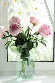 Una vista di un bouquet di peonie rosa in piedi in un vaso sulla finestra. sfondo di concetto, fiori, vacanze.