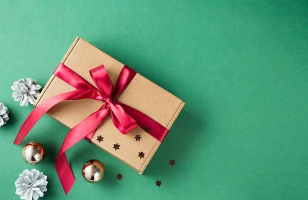 Vista su confezione regalo marrone e nastro rosso su sfondo verde. il concetto di regali per capodanno e natale.