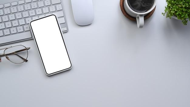 Sopra vista uomo d'affari utilizzando smart phone alla scrivania in ufficio.
