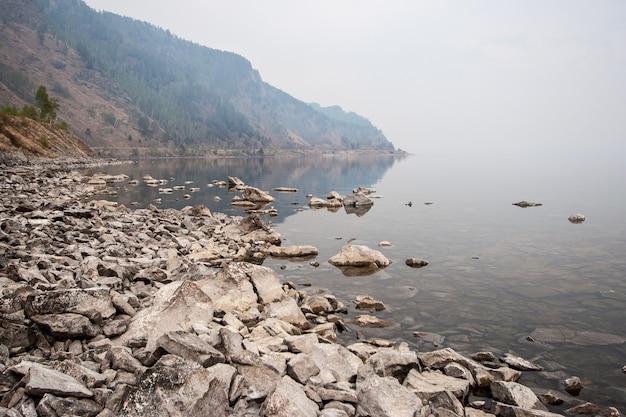 Vista del promontorio vicino all'acqua nella nebbia