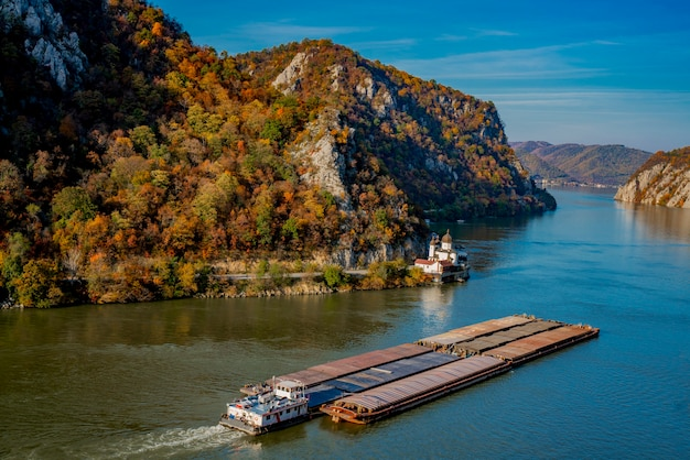 Vista alla nave da carico che passa dal monastero di mraconia sul lato rumeno della gola di djerdap del fiume danubio