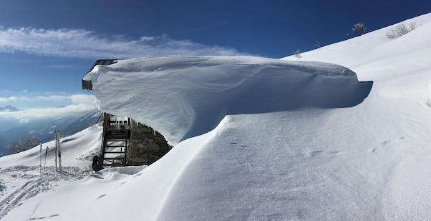 Vista su uno chelet coperto di neve sulla montagna alpina con sci da alpinismo sulla neve