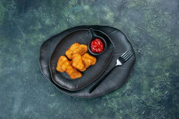 Vista dall'alto di pepite di pollo e forchetta per ketchup in lastre nere su superficie scura