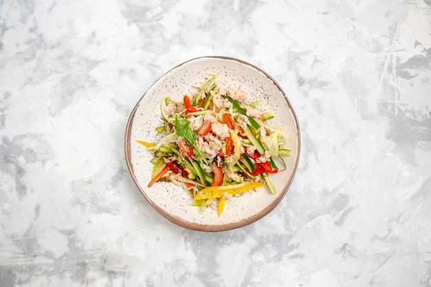 Sopra la vista dell'insalata di pollo con verdure su una superficie bianca macchiata con spazio libero