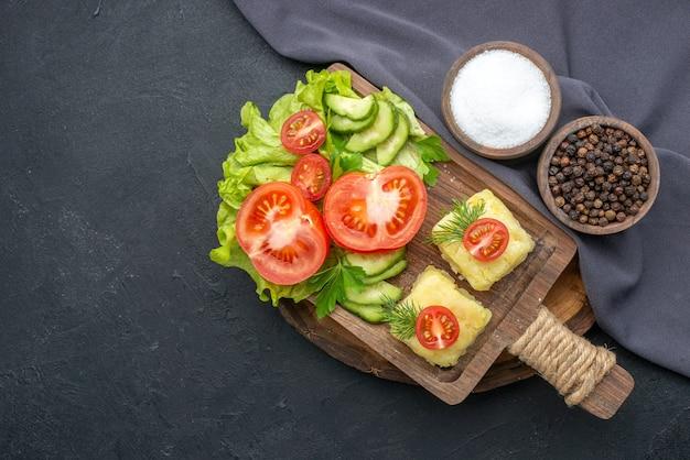Sopra la vista di verdure fresche tritate formaggio su tagliere e spezie su asciugamano di colore scuro su superficie nera