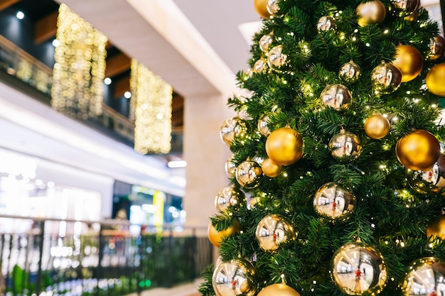 Vista di un albero di natale in primo piano con lo sfondo sfocato di un centro commerciale