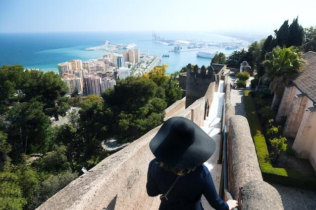 Vista della città di malaga con una donna con cappello sulle scale dell'alcazaba