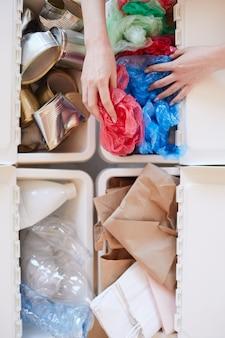 Vista sopra ravvicinata di un irriconoscibile donna che mette il sacchetto di plastica scartato nel cestino della spazzatura durante lo smistamento dei rifiuti a casa