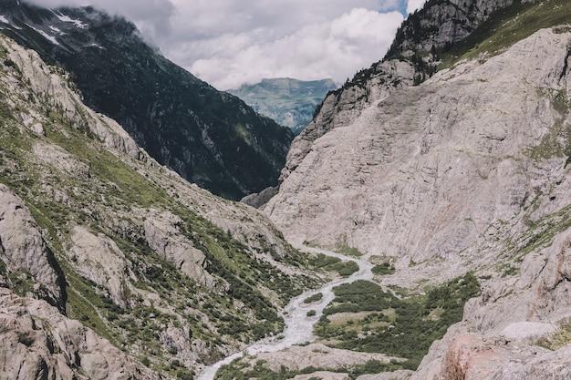 Visualizza le scene del fiume del primo piano in montagne, parco nazionale svizzera, europa. paesaggio estivo, tempo soleggiato, cielo azzurro drammatico e giornata di sole